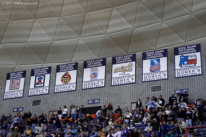 Gampel Pavilion is ringed with signs and banners lauding both UConn basketball programs, capped by the Women's National Champs section